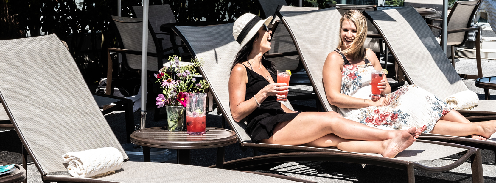 Two women sharing a laugh on pool lounge chairs