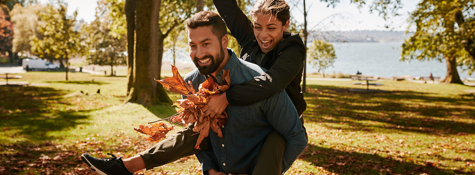 Couple playing with leaves in Vancouver park